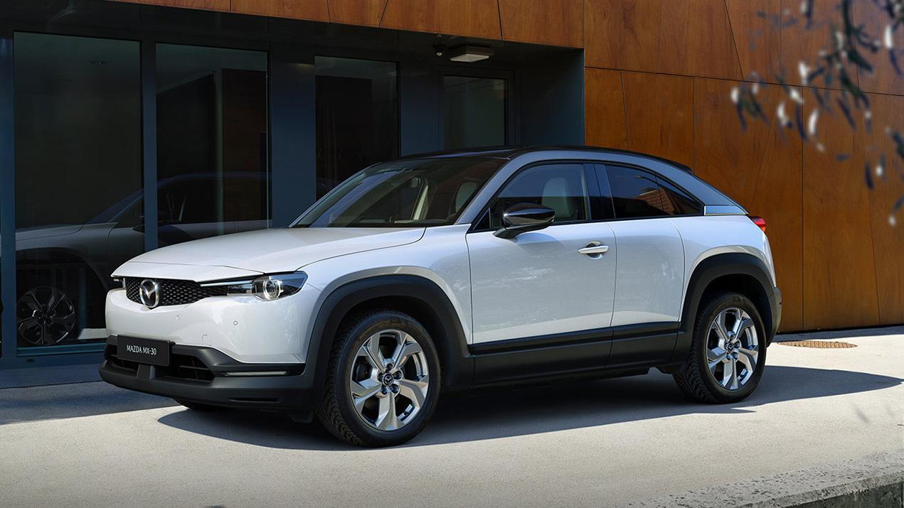 El precio inicial es muy competitivo para un SUV de su tipología (US33.500, unos 120 millones de pesos aproximadamente), y considerando que la marca tiende a equipar sus vehículos con características y materiales que normalmente se encuentran en autos premium. Es la primera incursión de Mazda en los vehículos eléctricos, y se comercializará a un costo menor que el Volkswagen ID.4. Su autonomía con una sola carga será de 100 millas, 160 kms con su batería de iones de litio de 35,5 kWh. Es una cifra muy baja para un vehículo eléctrico en estos días. Incluso el Mini Cooper SE de 182 km o el Nissan Leaf base de 240 km lo superan; un Kona EV y un ID.4 alcanzan un máximo de 420 kilómetros. Mazda, sin embargo, dice que se eligió la batería más pequeña para preservar la dinámica de manejo y minimizar el impacto ambiental. Tener solo 160 kilómetros de autonomía, dicen los expertos, creará una seria ansiedad por el alcance, y eso reducirá la cantidad de personas dispuestas a comprar el MX-30. Mazda entregará de forma gratuita durante los primeros tres años el Connected Services, que permite a los propietarios monitorear sus vehículos a través de una aplicación para teléfonos inteligentes. El software también permite a los propietarios encender y apagar el automóvil a distancia, verificar los niveles de la batería, acceder al sistema de control de clima y bloquear o desbloquear las puertas. Mazda dice que la batería llega al 80% de su carga en 36 minutos con un cargador rápido de 50 kW de nivel 3. Con uno de nivel 2 le tomará 2 horas y 50 minutos, y con uno de nivel 1 hasta 13 horas y 40 minutos. Mazda también ofrece una garantía de ocho años y 160,000 kilómetros para la batería. El MX-30 EV básico viene lleno de funciones. El equipo estándar incluye una pantalla central de 8.8 pulgadas con conectividad Apple CarPlay y Android Auto. Características de lujo como asientos delanteros con calefacción, volante y selector de marchas forrados en cuero, techo corredizo eléctrico, espe